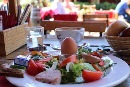 Köstliche regionale Wurstvariationen, ein frisch gekochtes Ei und knuspriges Brot.