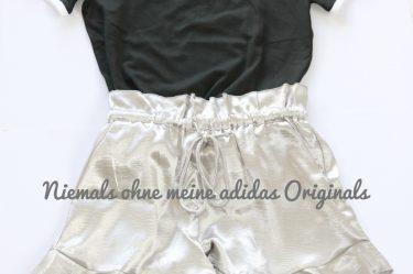 Die drei adidas Streifen sind Kult - frech kombiniert mit rüschigen Silbershorts.