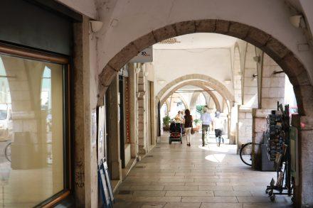 Die Arcaden der Laubengänge spenden Schatten und rahmen das Stadtbild malerisch ein.