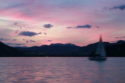 Ein einsames Segelboot kreuzt den Lago di Caldonazzo im Sonnenuntergang.