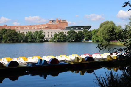 Tretbootverleih am Dutzendteich mit Blick auf die Kongresshalle und das Dokumentationszentrum.