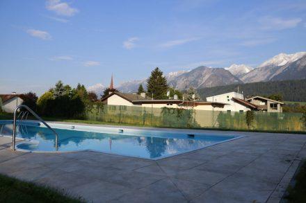Im Pool spiegelt sich die herrliche Bergwelt samt Kirchturm von Volders.