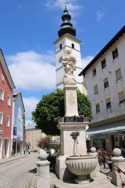 Am Platz in Waging mit Blick auf Brunnen und Kirche.