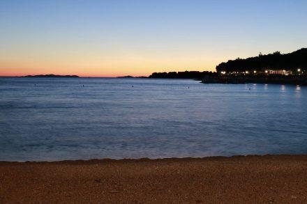 Blick von der Flaniermeile in Primosten auf das Meer und den Sonnenuntergang.