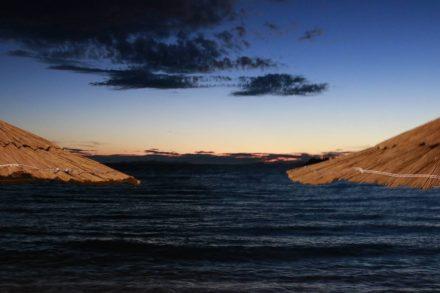 Stimmungsbild mit zwei Sonnenschirmen, Meer und romantischem Abendlicht in Primosten.