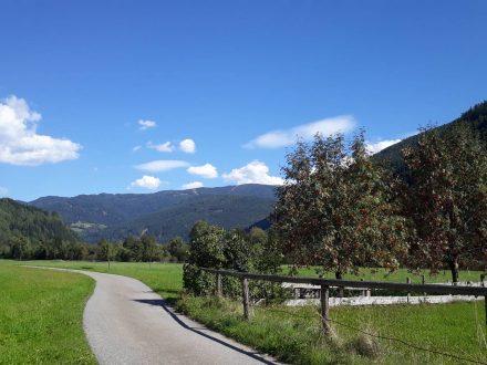 Eingerahmt von waldigen Hügeln durchquert man satte, grüne Wiesen.