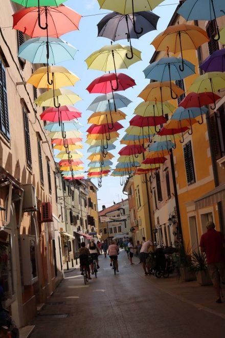 Bunte Häuser und bunte Schirme in den Gassen von Novigrad.