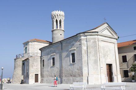 Die weiß gekalkte Mutter Gottes Kirche an der Uferpromenade von Piran.