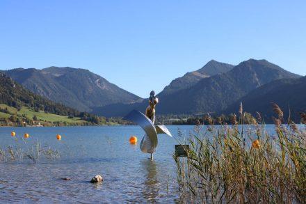 Moderne Kunst im See, eingerahmt von den bayerischen Bergen.