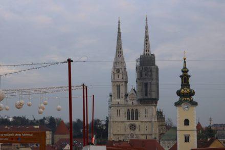 Die Deko des Weihnachtsmarkts im Vordergrund, dahinter Dom und Jelacica Kirchtürme.