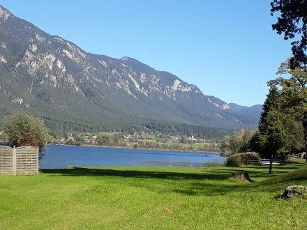Der Presseggersee mit seinen grünen Badewiesen und Förolach im Hintergrund.