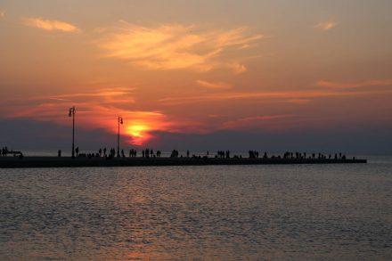 Wie ein Scherenschnitt sieht dieses Sonnenuntergangs-Bild an der Mole in Triest aus.