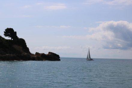 Aus der Bucht von Ulcinj segelt ein Boot aufs Meer hinaus.