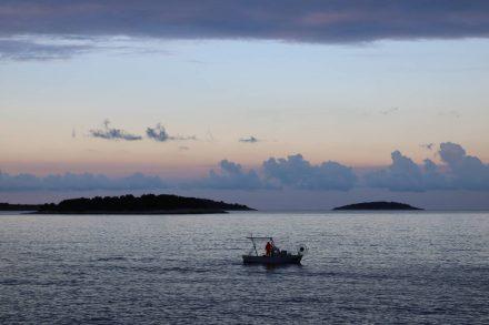 Früh am Morgen tuckert ein Fischerboot vor der Küste von Primosten.