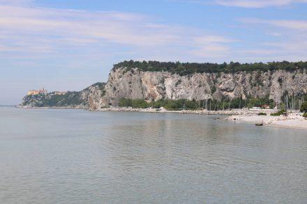 Das Schloss von Duino, der Rilke Weg oben auf dem Felsplateau und darunter der Strand von Sistiana.