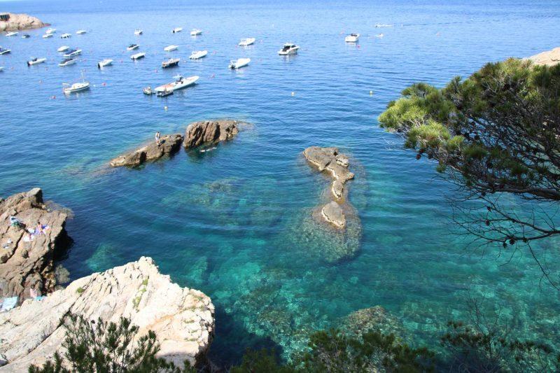 Fast wie ein Gemälde wirken die Felsformationen, das türkise Meer und die weißen Boote.