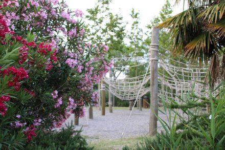 Viele Bäume, Hecken und blühende Sträucher unterteilen das Rubina Resort und rahmen den Kletter-Spielgarten ein.