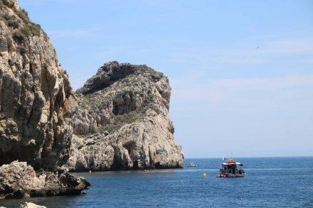 Unter den majestätischen Felswänden wirken die Boote winzig klein.