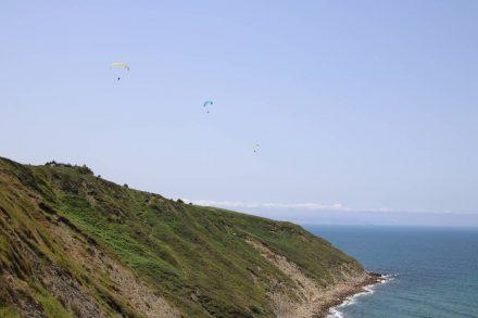 Hoch über der Steilküste ziehen die Drachenflieger ihre Bahnen.