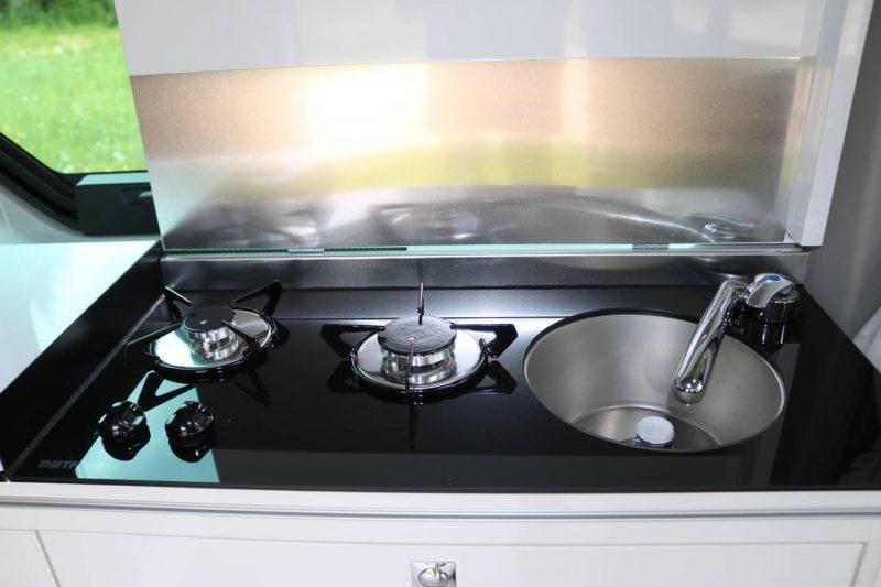 Zwei-Flammen-Gasherd und Waschbecken im Küchenblock.