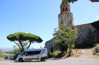 Parkplatz unter Zypressen an der alten Festungsmauer.