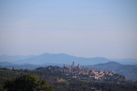 Auf dem Weg nach Volterra zeigen sich die Türme von San Gimignano das erste Mal.