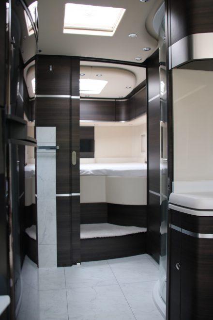 Blick durch das Bad zum Schlafbereich mit hellen Böden und eleganter, dunkler Holzoptik.