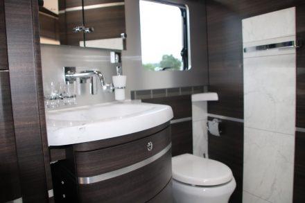 Elegant in dunklem Holz und hellen Sanitäreinrichtungen das großzügige Bad mit Häcksler-Toilette.