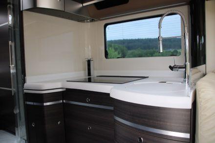Gas-Ceran-Kochfeld, versenkbare Steckdosenleiste und eine absenkbare Kaffeemaschine in der Küche des Concorde Centurion Luxus Wohnmobils.
