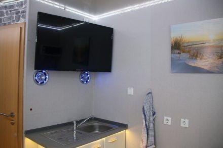 Der zweite Fernseher mit den beleuchteten Boxen hängt über der Spüle