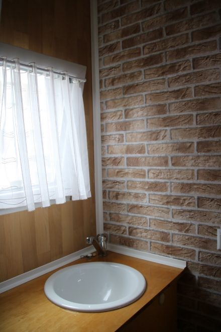 Badezimmer mit Waschtisch, Unterschrank, Fenster und Ziegeltapete