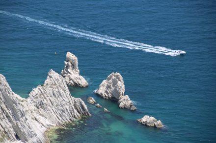 Im türkisfarbenen Wasser stehen die zwei Felsen Due Sorelle vor der Bucht Wache