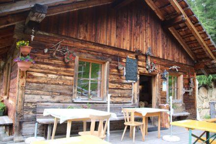 Die gemütliche Steinzger Alm lädt zu einer Pause hoch über dem Antholzer See in Südtirol ein