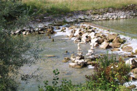 Meditative Steintürmchen in der glasklaren Mangfall