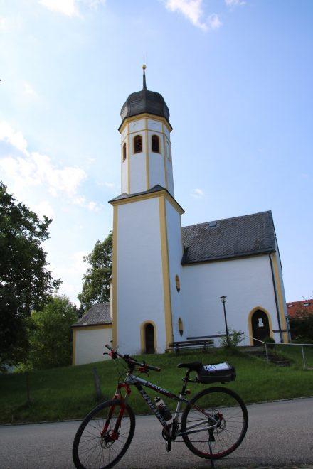 Der Crosser vor der idyllischen Wallfahrtskirche Mariä Opferung in Überreit