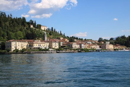 Unter Hügeln mit Zypressen liegen die bunten Häuser von Bellagio auf der Halbinsel im Comer See
