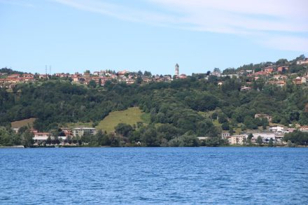 Vom Ostufer aus sieht man den Kirchturm von Galbiate auf dem Hügel