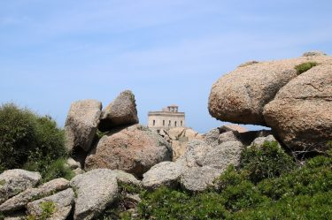 Wild aufgetürmte Granitfelsen rahmen den Leuchtturm ein