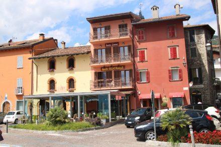 Bunte Häuserfassaden und gepflegte Grünflächen in Gravedona
